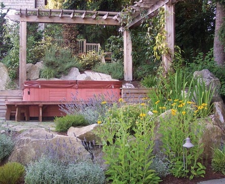 Arbor surrounds hot tub and supports plants that offer privacy