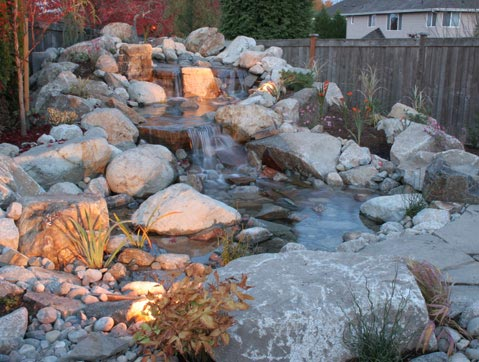 Waterfall over river rock and stone rock designed by Environmental Construction Inc. in Kirkland WA